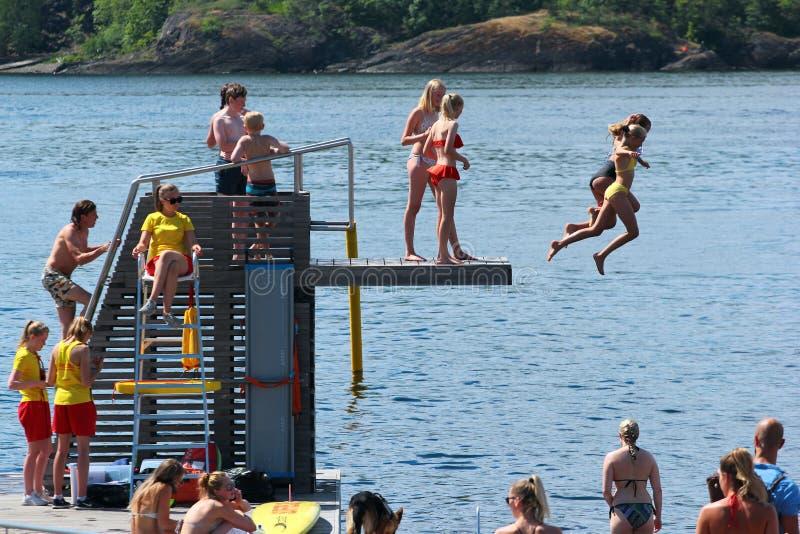 Folket dyker in i vatten och solbadar i Oslo, Norge arkivbild