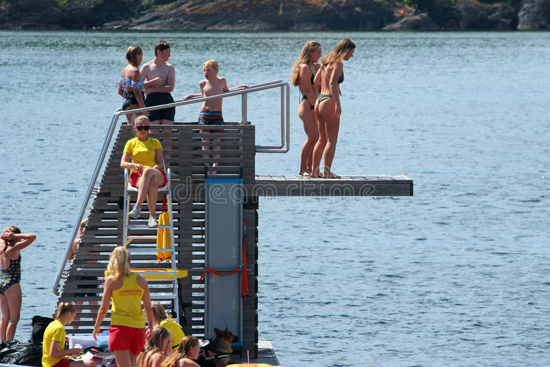 Folket dyker in i vatten och solbadar i Oslo, Norge royaltyfri fotografi