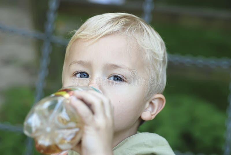 Folket ett barn av tre år är dricksvatten från en plast- flaska i parkera royaltyfri bild