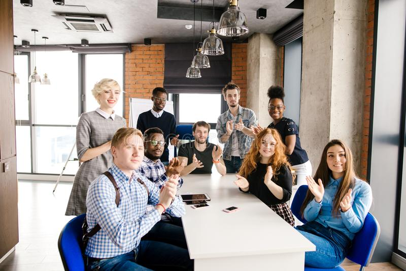 Folket för blandad grupp applåderar deras händer jobbet har gjort arkivfoton