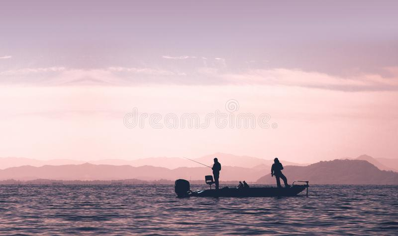 Folket fiskar på det bas- fartyget i sjön arkivbild
