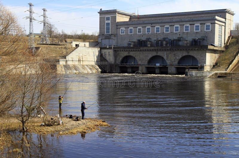 Folket fiskar på floden Narva mot bakgrunden av vattenkraftstationen royaltyfri foto