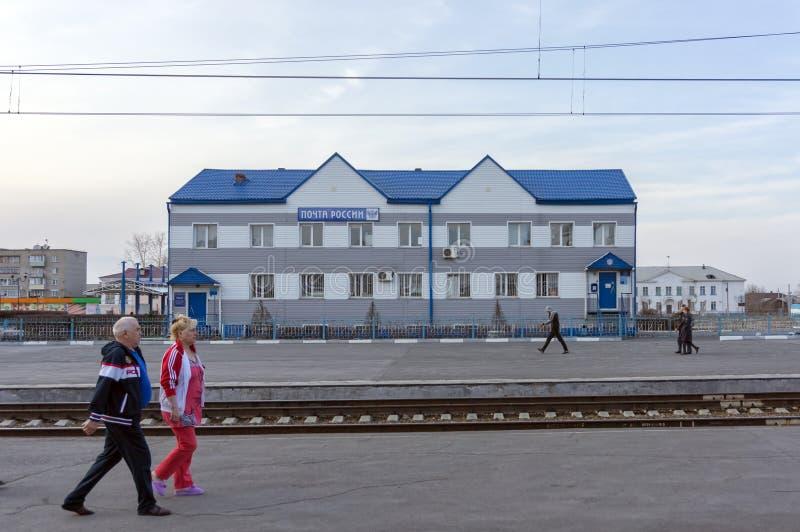 Folket går förbi kontoret av en rysk stolpe för stort ryskt förbundsstatföretag på en järnvägsstation i den Siberian staden arkivbilder