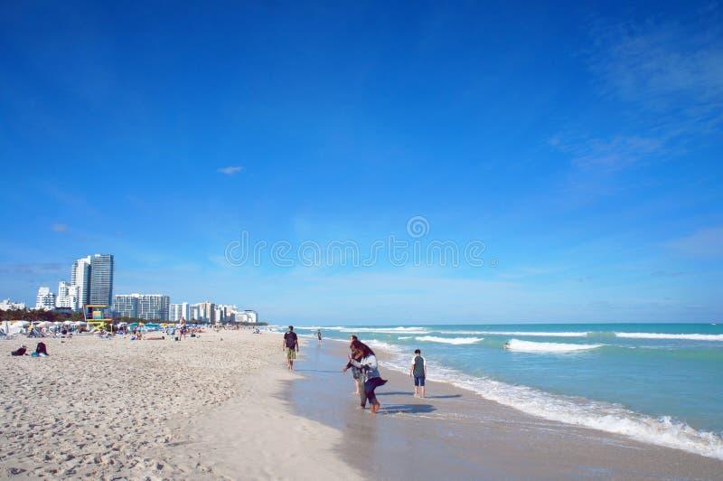 Folket går på den soliga södra stranden av Miami arkivfoton