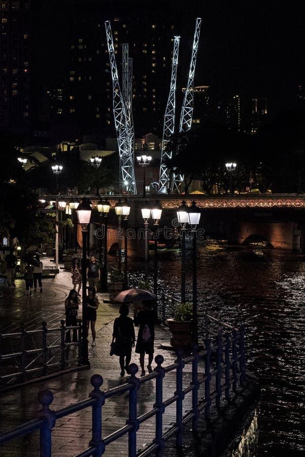 Folket går vid floden under ett ljust regn i Singapore arkivbild