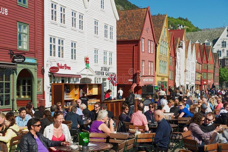 Folket har lunch på gatarestauranger på Bruggen i Bergen, Norge royaltyfri fotografi