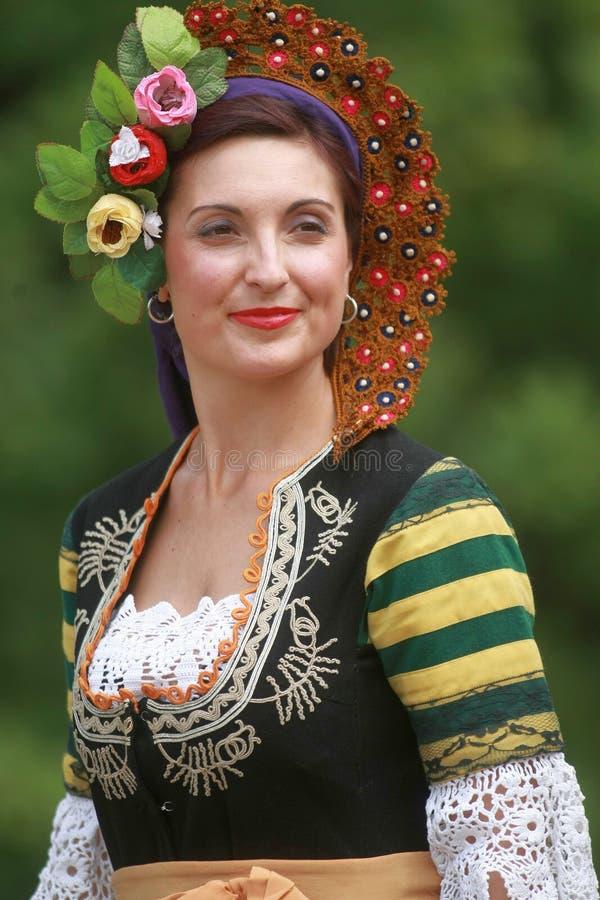 Folket i traditionella dräkter dansar bulgarian horo en äng royaltyfria bilder