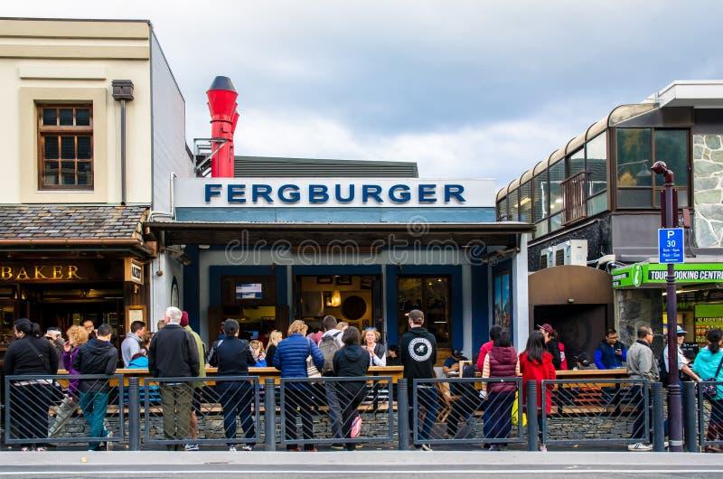Folket kan sett köa och att vänta deras foods framme av Fergburger'sens restaurang i Queenstown arkivbild