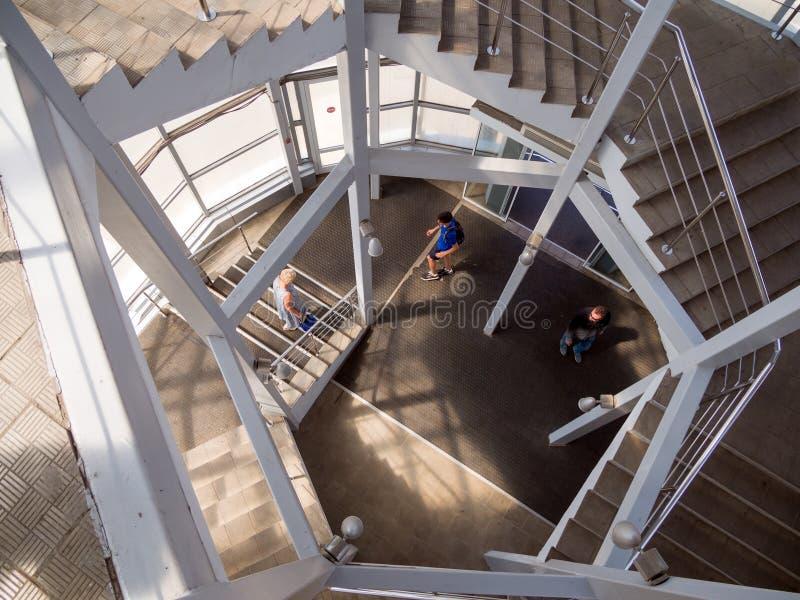 Folket klättrar spiraltrappuppgången av den fot- planskilda korsningen arkivbilder