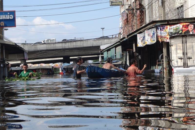 Folket klarar av med vattnet i en översvämmad gata i Rangsit, Thailand, i Oktober 2011 royaltyfri bild