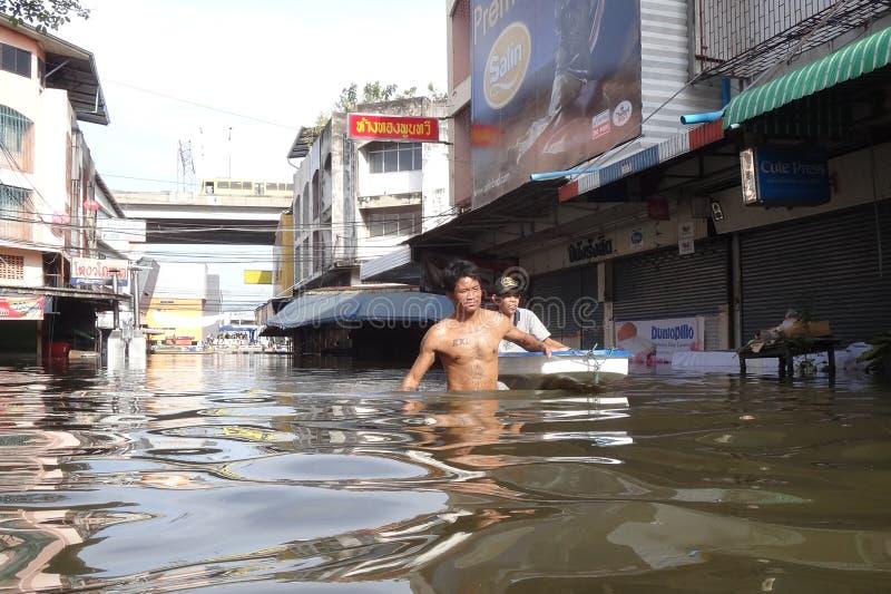 Folket klarar av med vattnet i en översvämmad gata i Rangsit, Thailand, i Oktober 2011 royaltyfria foton