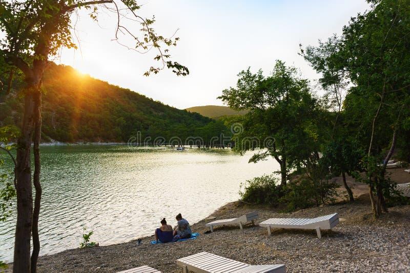 Folket kopplar av på kusten, når de har simmat i cypress sjön Solnedg?ng arkivbilder