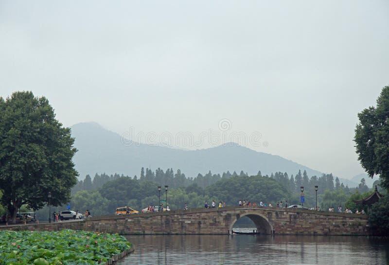 Folket korsar den västra sjön i Hangzhou vid bron royaltyfri foto