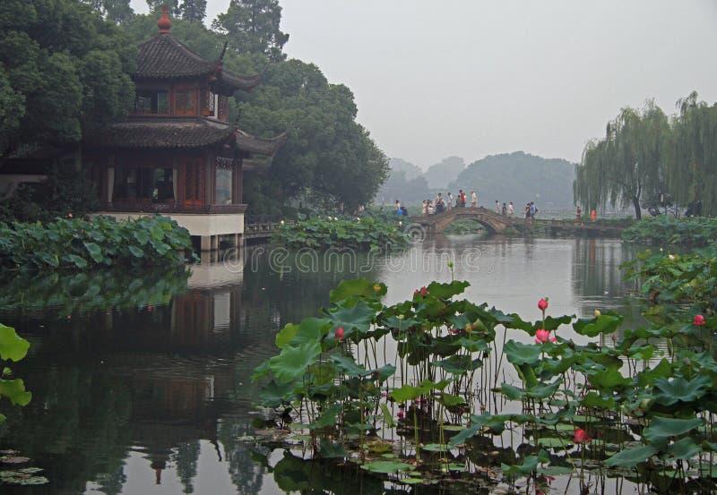 Folket korsar den västra sjön i Hangzhou vid bron fotografering för bildbyråer
