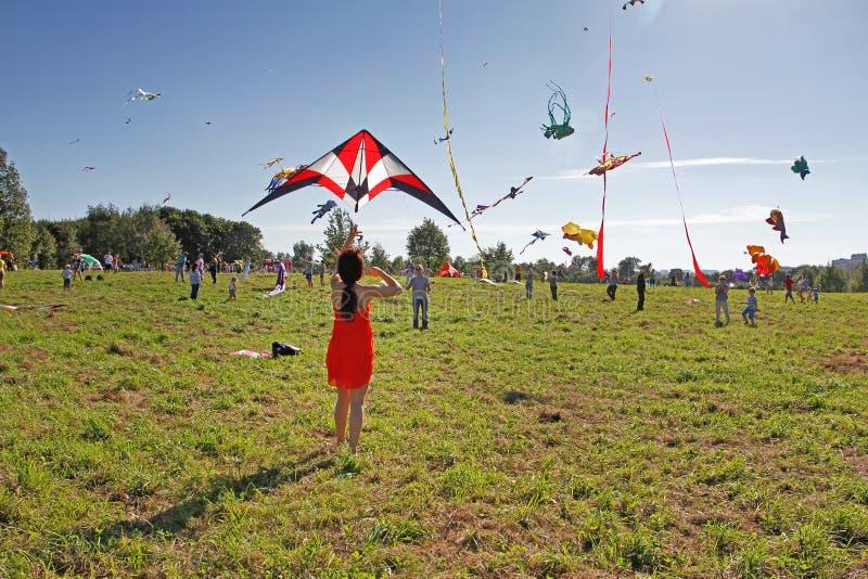 Folket lanserar nyckelpigadraken in i himlen på drakefestivalen i parkera Tsaritsyno i Moskva arkivbilder