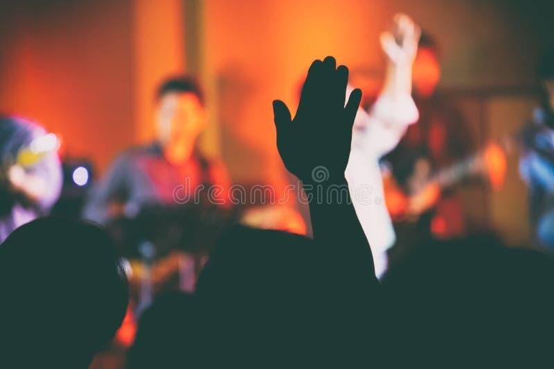 Folket lyfter dem räcker upp för att tillbe Jesus i den inomhus dyrkankonserten fotografering för bildbyråer