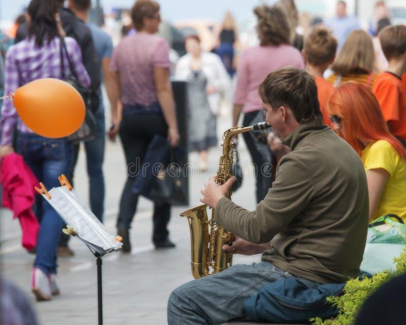 Folket lyssnar till en gatamusiker royaltyfri fotografi