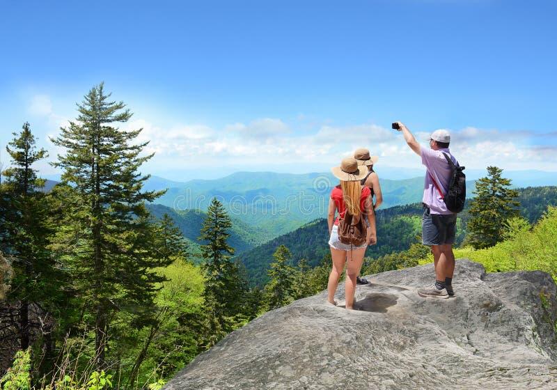 Folket med ryggsäckar som fotvandrar på sommar, snubblar i berg arkivbilder