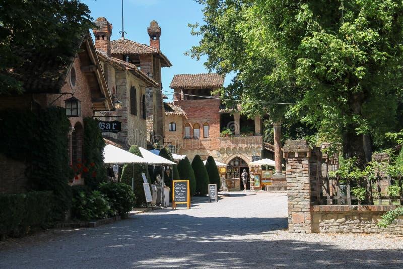 Folket nära liten turiststänger och souvenir shoppar i Grazzano VI arkivbilder