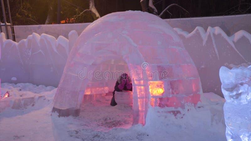 Folket och behandla som ett barn går i isstad under snöfall Barnlekar på igloo i isstaden, snöby Is för ` s för nytt år royaltyfria foton