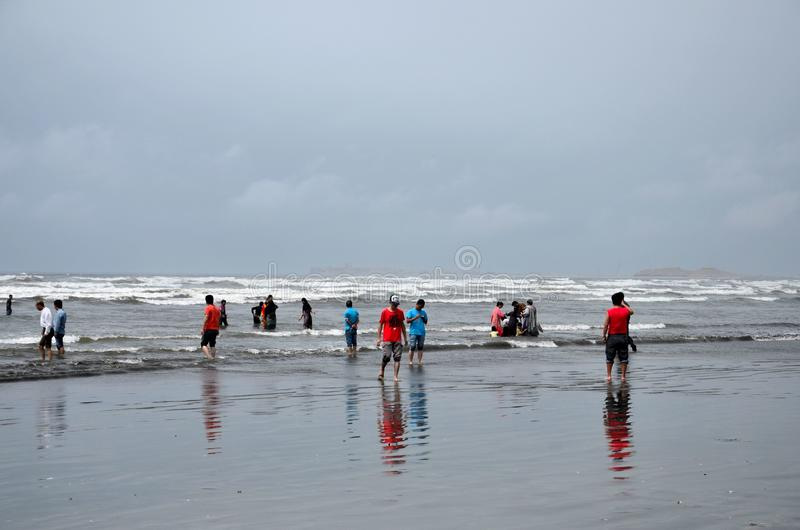 Folket och familjer vadar i vatten och tycker om vågorna på havssiktsstranden Karachi Pakistan arkivbilder