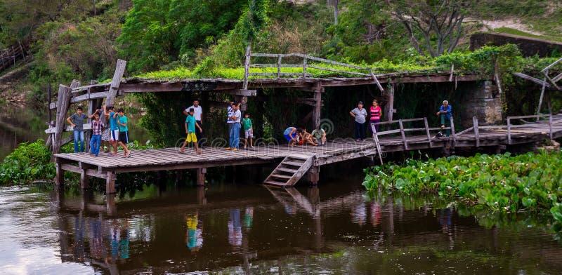 Folket på bryggan som välkomnar Aquidabanen, sänder på Rio Paraguay fotografering för bildbyråer