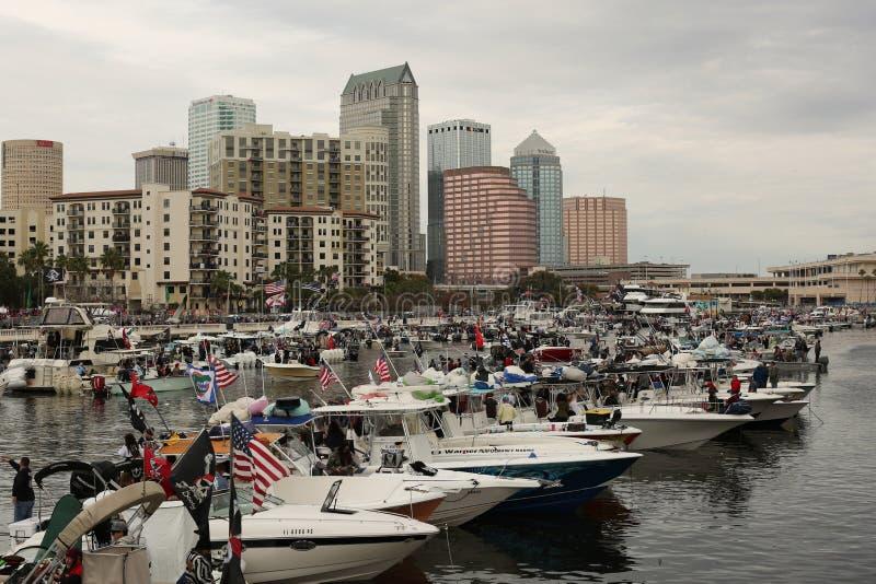 Folket på kustlinjen och fartyg i vattnet med sikt av staden på piratkopierar razzia under Gasparilla i Tampa, Florida Januari 2 royaltyfri foto