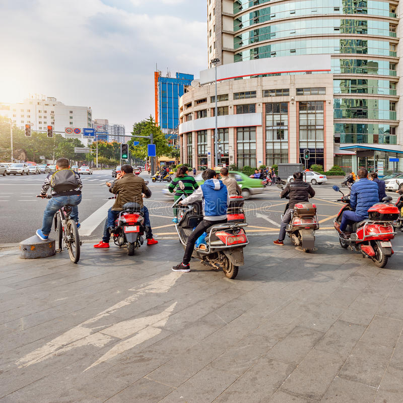 Folket på mopederna väntar vid tvärgatan royaltyfri foto