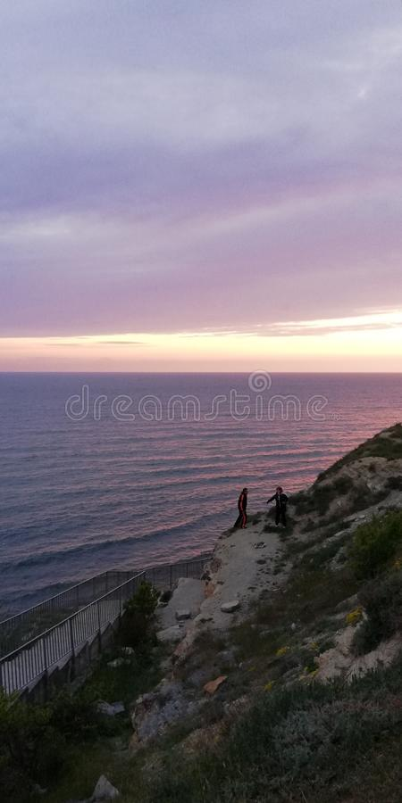 Folket p? vaggar mot solnedg?nghavslandskapet Havet och himlen m?las i rosa och purpurf?rgade f?rger Scenisk bakgrund arkivfoto