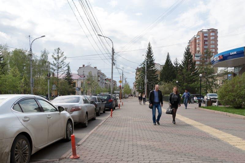 Folket promenerar Mira Avenue förbi bilar som står på sidan av vägen, i det gamla centret av Krasnoyarsk, på våren royaltyfria foton