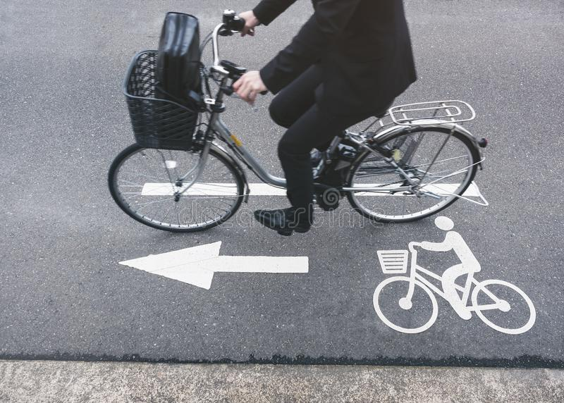 Folket rider cykeln på Signage för vägcykelgränd arkivfoto