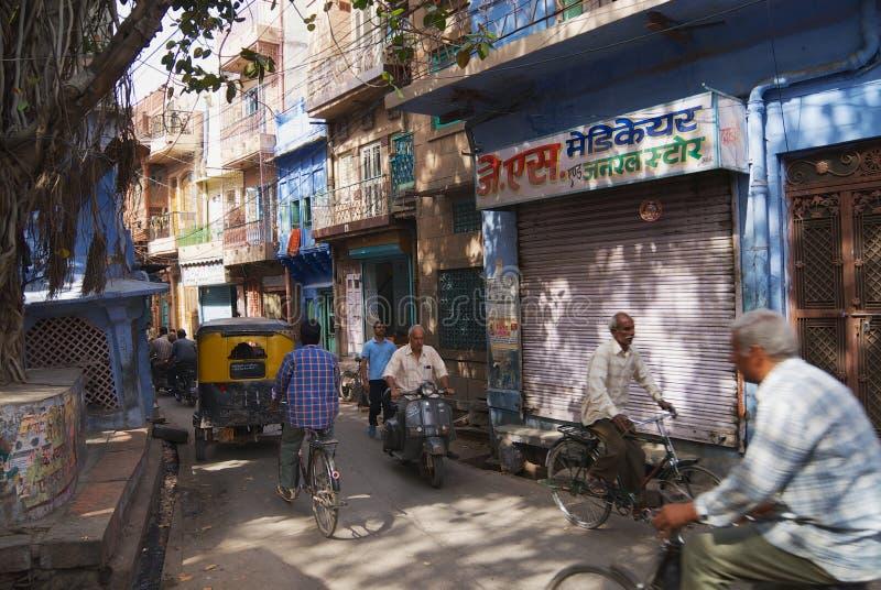 Folket rider cyklar på den smala gatan i historisk del av Jodhpur, Indien royaltyfria bilder