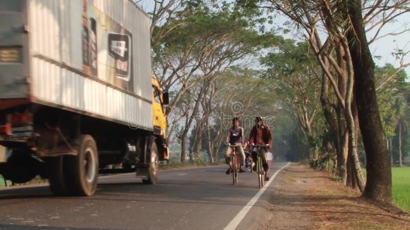 Folket rider cyklar vid vägen i Jessore, Bangladesh lager videofilmer