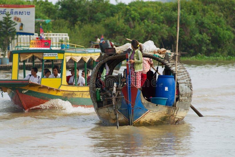 Folket rider det traditionella tr?fartyget p? Tonlen underminerar sj?n i Siem Reap, Cambodja royaltyfri fotografi