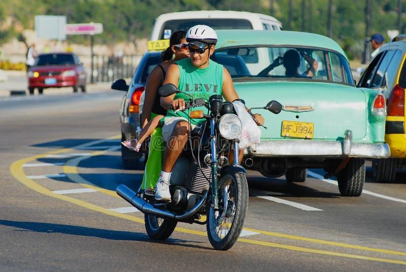 Folket rider mopeden vid den Malecon avenyn i havannacigarren, Kuba arkivbilder