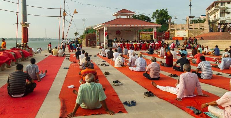 Folket samlade för morgonyoga på Assi Ghat på banken av floden Ganga i Varanasi royaltyfria foton