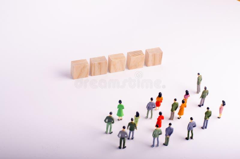 Folket ser en träkub stående fem med bokstäver på en vit bakgrund Ställe för bokstäver på fyrkanterna utförd ungdom för mall för  arkivbilder