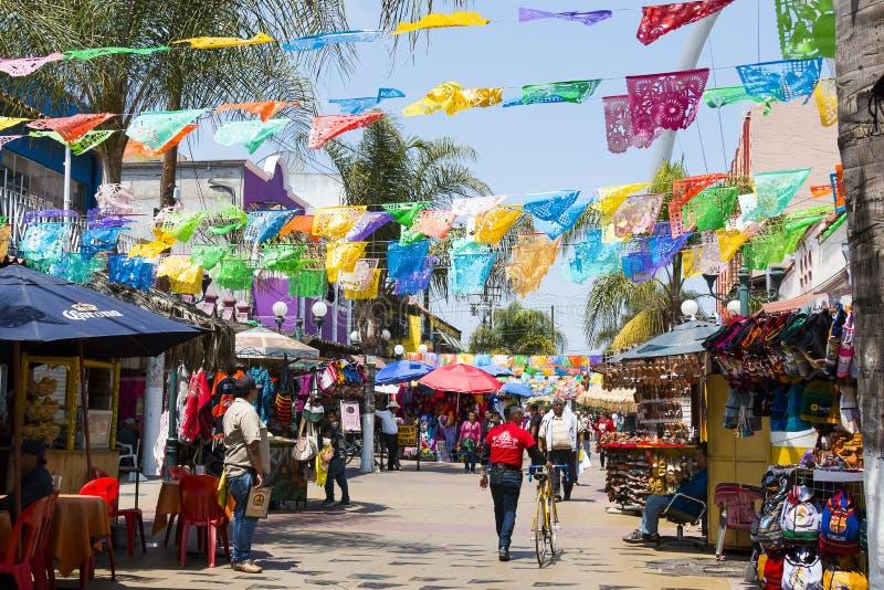 Folket shoppar under hängande flaggor i Tijuana, Mexico royaltyfri foto