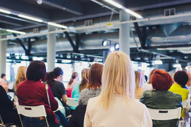 Folket sitter i fåtöljer i konferensrum, fokus på blond kvinnanacke arkivbild