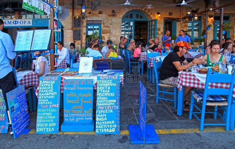 Folket sitter i trottoargatakafé i Chania strand på Kreta arkivbilder