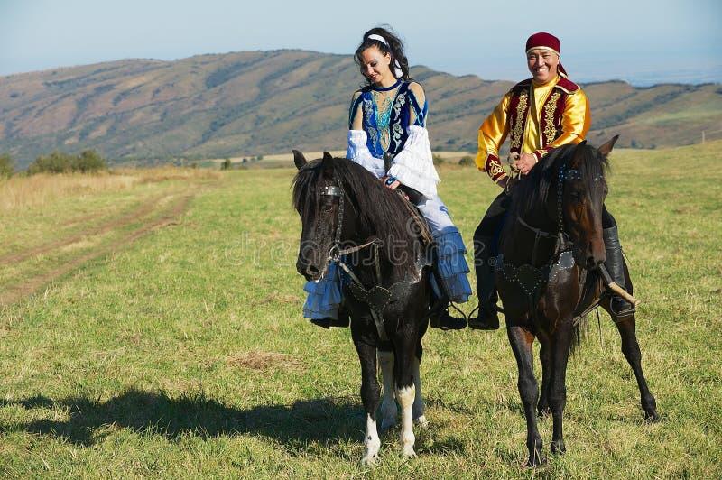 Folket som bär traditionella nationella klänningar, rider på hästrygg på bygd, Almaty, Kasakhstan arkivfoto