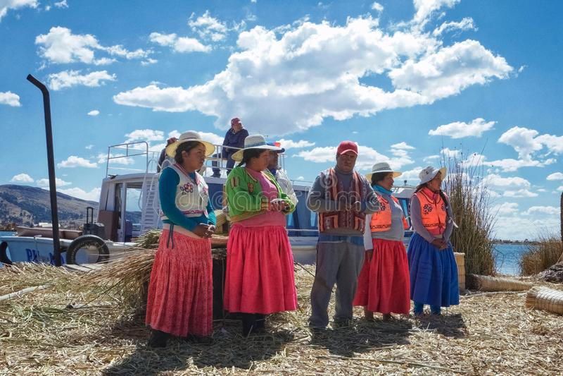 Folket som bor på vassön av sjön Titicaca, introducerar sig och berättar turister berättelser om hur dem som gör l royaltyfria bilder