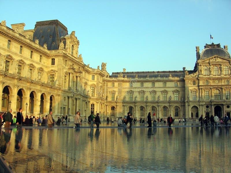 Folket som går i Louvremuseet Paris Frankrike, reflekteras i vattnet av springbrunnen Paris Frankrike royaltyfri foto