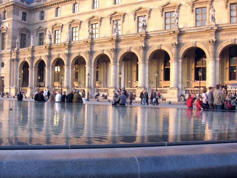 Folket som går i Louvremuseet Paris Frankrike, reflekteras i vattnet av springbrunnen Paris Frankrike royaltyfri bild