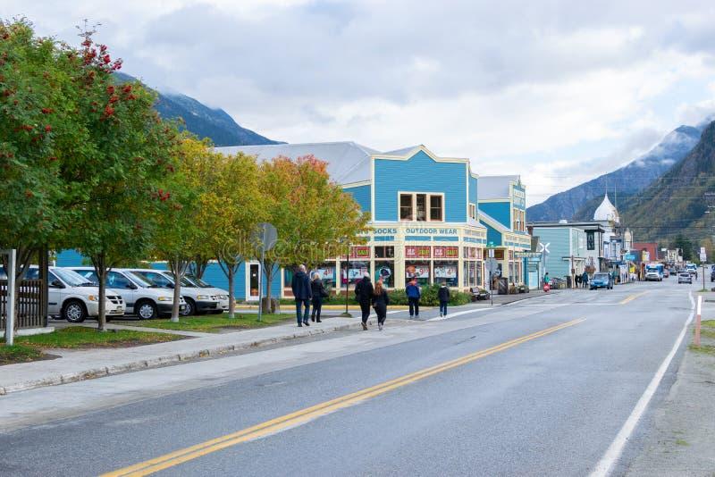Folket som går, och bilkörning förbi shoppar på Main Street i Skagway Alaska royaltyfria bilder