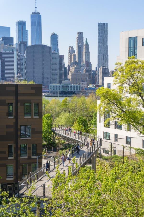 Folket som går på en gångbana in mot den Brooklyn bron, parkerar i New York City royaltyfri foto