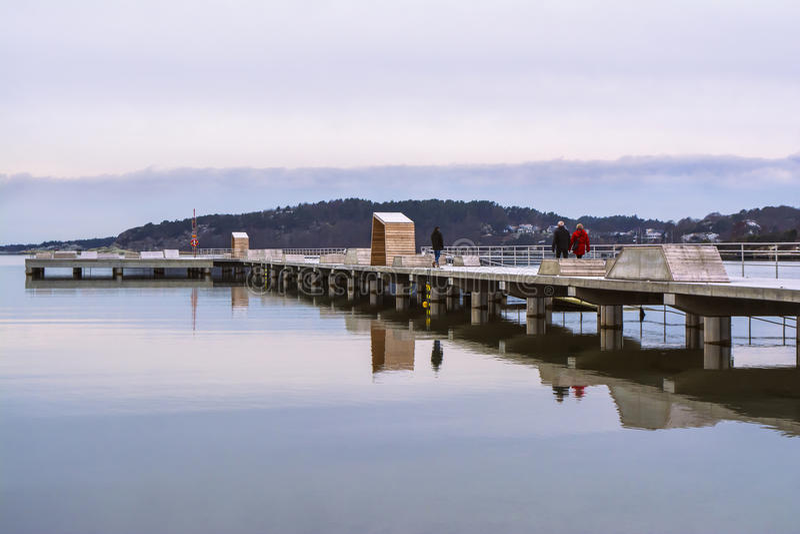 Folket som går på en lång pir, reflekterade i vattnet, på en lugna vinterdag arkivbild