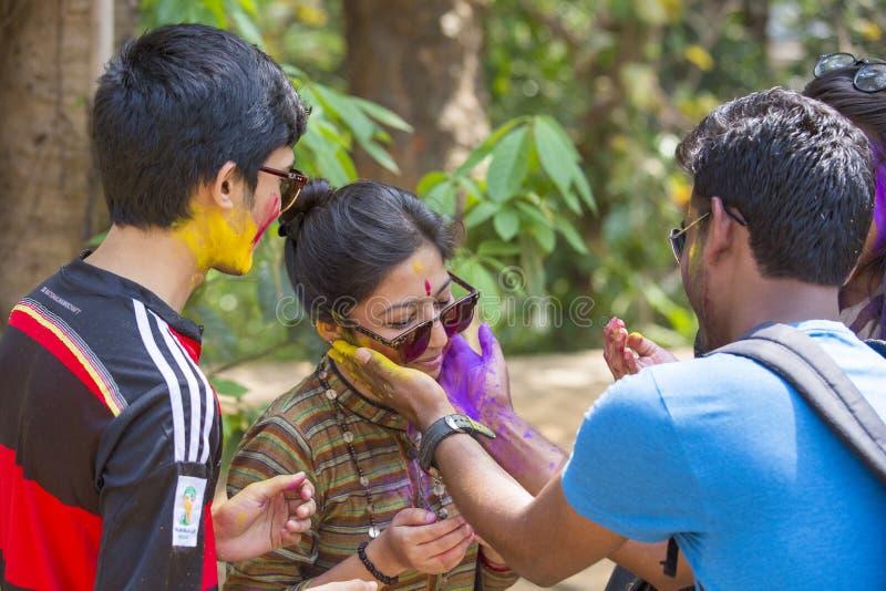 Folket som täckas i färgrikt pulver, färgar att fira Holi den hinduiska festivalen i Dhakah i Bangladesh arkivfoton