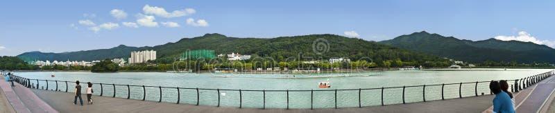 Folket som vilar vid sjön i stad, parkerar med berg i baksida fotografering för bildbyråer