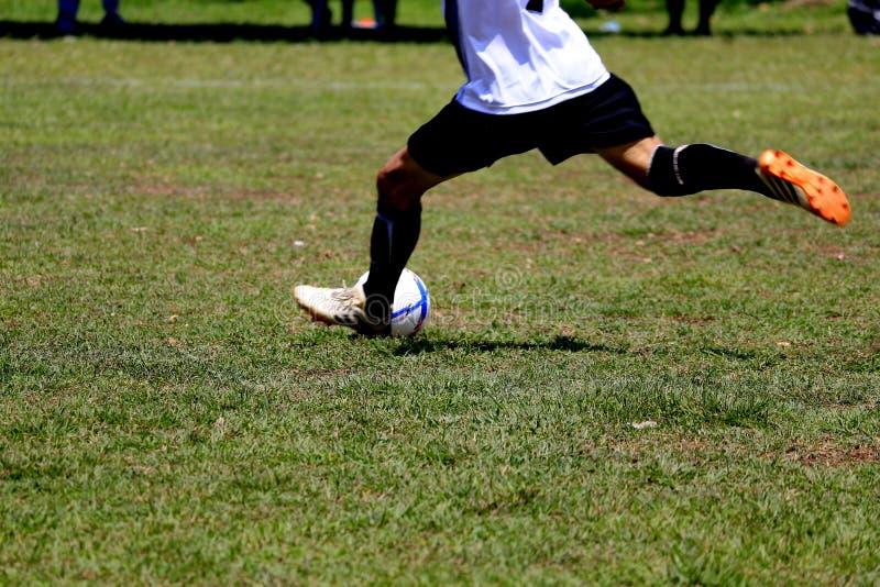 Folket spelar fotboll på en utomhus- gräsmatta arkivbilder